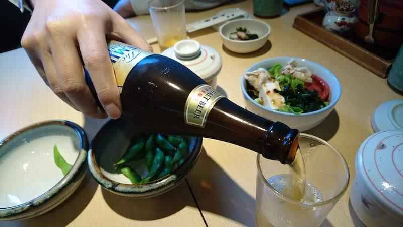 調布寿司祭り「大漁旗」瓶ビールをグラスに注ぐ